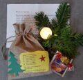 Weihnachtstüte des Heimatvereins, mit Brief, Teebeutel, Schokolade und Kerze an einem Tannenzweig.