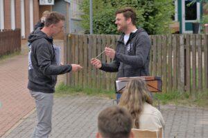 Rainer und Claus bei der Übergabe auf dem Platz vor dem ehemaligen Schützenhaus, Claus hält den Stab, Rainer greift danach, beide lächeln.