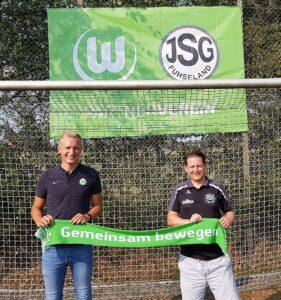 Vor einem Fussballtor stehen zwei Männer und halten ein Banner in den Händen, auf dem steht: Gemeinsam bewegen.