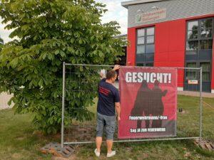 Das rote Feuerwehrhaus im Hintergrund. Mirco vom Förderverein hängt das Banner an ein aufgestelltes großes Gitter. Auf dem Banner zwei Schattengestalten und der Text: Gesucht! Feuerwehrmann/frau. Sag Ja zur Feuerwehr.