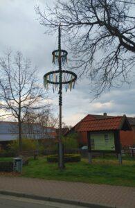 Maibaum mit zwei Ringen, zwischen zwei Eichen und neben einer Informationstafel. Im Hintergrund Gehöfte und ein bedeckter Himmel.