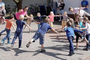 Kinder tanzen im Kreis.