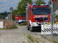 Auf der Straße vor der Schule halten zwei Einsatzfahrzeuge der Feuerwehr.