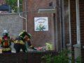 Zwei Feuerwehrleute bringen Schlauchkästen vor den Eingang, im Hintergrund ist das Emblem Löwenzahnschule zu erkennen.