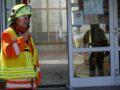 Der Einsatzleiter spricht ins Funkgerät, vor dem Eingang der Schule.