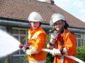 Zwei Feuerwehrleute beim Außeneinsatz am Rohr.