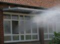Aus dem offnen Schulfenster trifft ein Wasserstrahl auf Dampf im Sonnenlicht.