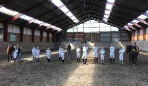 Die jungen Reiter bei der Urkunden-Übergabe in der Reithalle, alle tragen weiße Reitkleidung und schwarze Reitstiefel.
