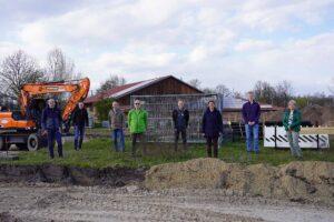 Mitglieder der SPD-Dollbergen stehen aufgereiht vor der Baustelle des Parkplatzes, im Hintergrund ein Bagger und die Mix-Firmenhalle.